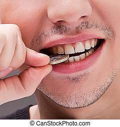 man with white teeth bites the coin