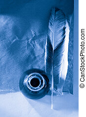 Feather and ink bottle on paper background
