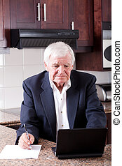 senior man doing internet banking at home and looks worried