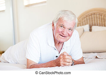happy elderly man lying on bed