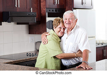 happy elderly couple hugging in home kitchen
