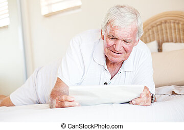 senior man reading newspaper - senior man lying on bed and...