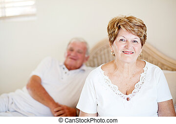 senior couple sitting on bed