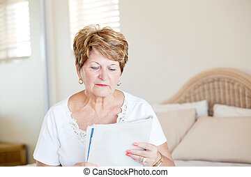 senior woman reading newspaper - senior woman sitting on bed...