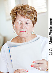 elderly woman reading newspaper