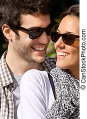 Close up portrait of smiling couple with sunglasses .