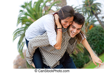 Cute girl piggybacking on boyfriend - Attractive young girl...