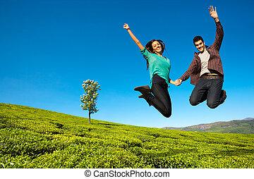 Happy couple jumping high - Happy couple jumping with hands...
