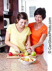 mother teaching teen daughter making fruit salad