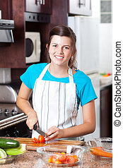 teen girl preparing salad in kitchen