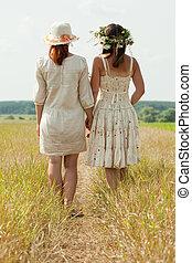 two women on summer field - Rear view of two women on summer...
