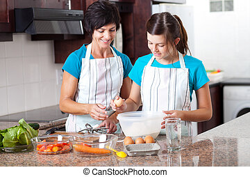 middle aged mother teaching teen daughter baking