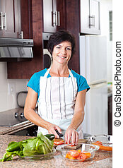 pretty middle aged woman cooking in kitchen