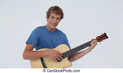 Smiling man holding his acoustic guitar against a white...