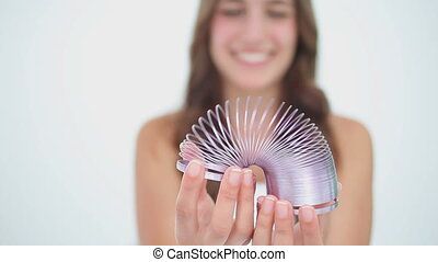 Happy brunette woman playing with a metal spring
