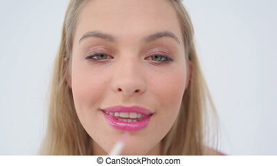 Blonde woman applying lip gloss on her lips against a white...