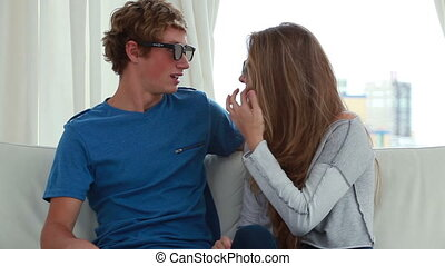 Happy couple playing while wearing 3D glasses in the living...