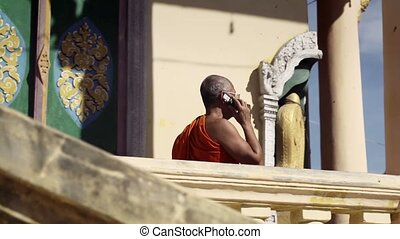 Old monk talking with mobile phone - Senior Asian buddhist...