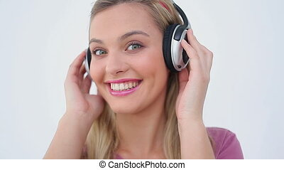 Smiling blonde woman listening to music against a white...