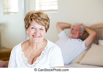 happy senior woman in bedroom with husband