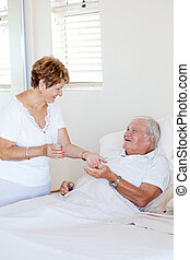 caring senior wife giving medicine to ill husband