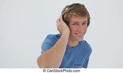 Happy young man listening to music against a white...