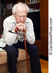 Old Man With Cane - unhappy old man sitting on a bed and...