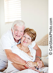 happy elderly couple hugging in bedroom
