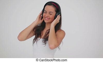 Happy brunette woman wearing headphones against a grey...