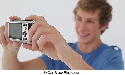 Smiling man taking himself in picture against a white...