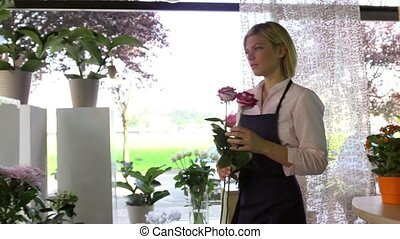 Pretty girl at work in flowers shop - Young attractive woman...