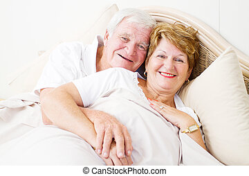 happy senior couple hugging in bed