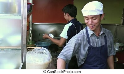 Men cooking Asian food as team - Two cooks preparing...