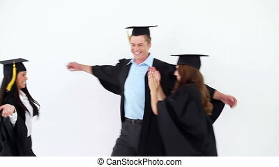 Cheerful graduated students hugging each other against a...
