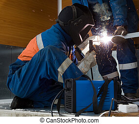 Welder working with a metal structure - A welder working in...