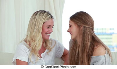 Happy young women talking to each other