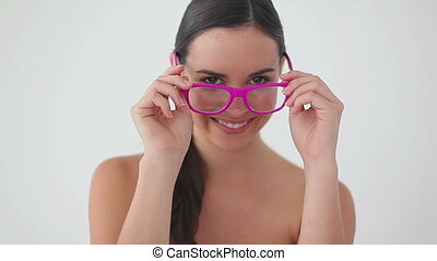 Smiling brunette woman wearing pink glasses