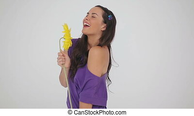 Smiling woman throwing a yellow flower against a grey...