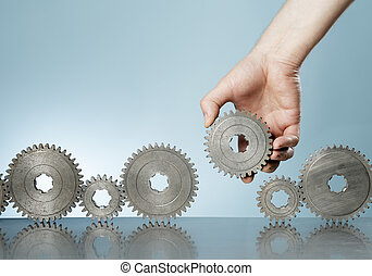 The Missing Piece - Man adding a cog gear in a row of old...