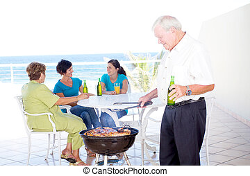 grandpa doing barbeque for the family on balcony