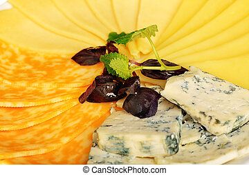 cheese assortm - Various types of cheese on a plate.
