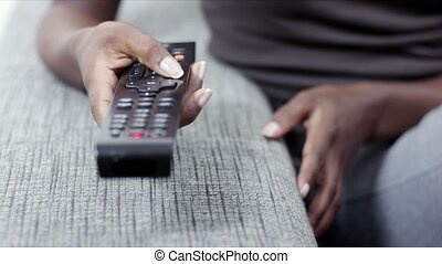woman holding tv remote control - closeup of woman on sofa,...
