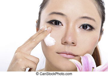 Skin care - woman applying creme on her face