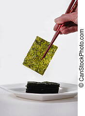 Roasted Seaweed, held with red chopsticks Isolated on white...
