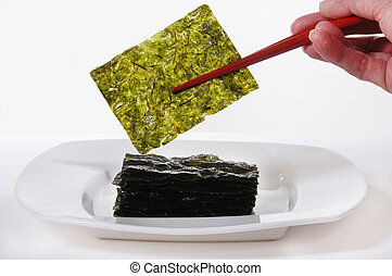 Roasted Seaweed, held with red chopsticks. Isolated on white...