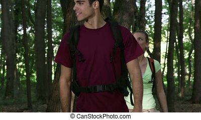young man and woman hiking in woods