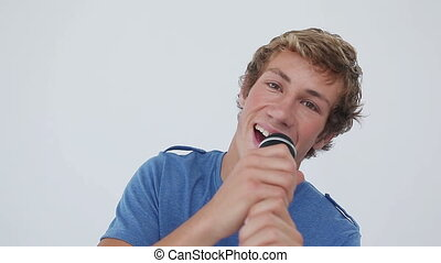 Happy young man playing karaoke against a grey background