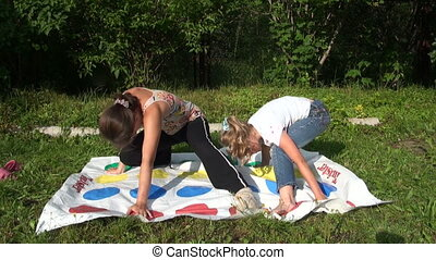 The mother with her daughter play twister