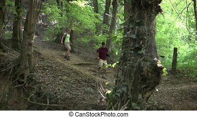 young couple trekking in forest - young man and woman...