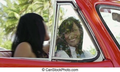 beautiful twin sisters in red car - young adult brunette...